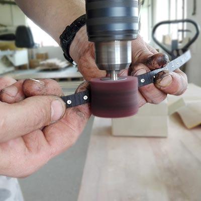le mani di un uomo che lavora i bracciali in legno Paul Cortese