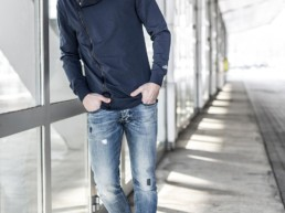 un uomo appoggiato a una vetrata indossa una felpa blu con zip Paul Cortese