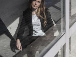 Ragazza dietro al vetro che indossa una t-shirt Paul Cortese