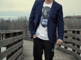Un uomo indossa una t-shirt Paul Cortese sotto una giacca blu